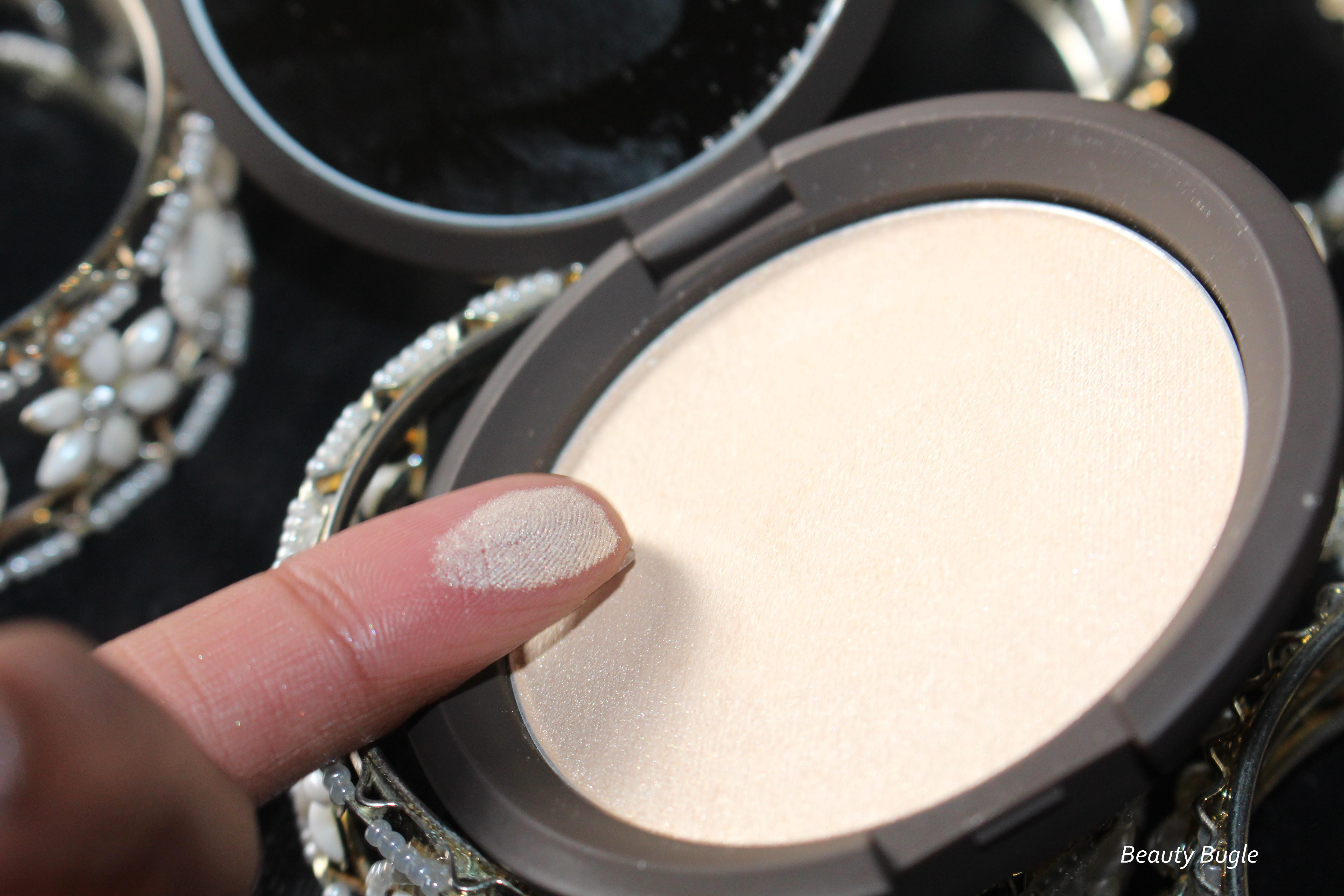 As you can see from the finger swatch, Becca's Shimmering Skin Perfector Pressed (Moonstone) is pretty white gold and you can detect a hint of chalkiness.